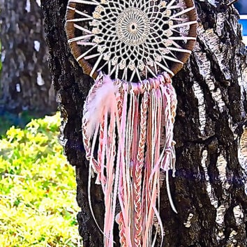 Dreamcatcher with crochet center, silk ribbons, braids, shells, and charms.