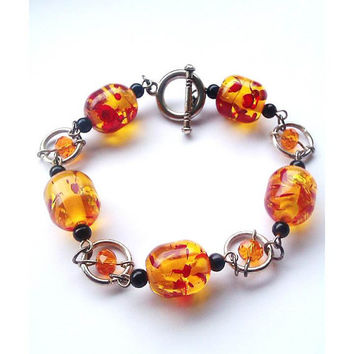 Orange Bead Bracelet With Small Black Beads and Orange Crystals Surrounded by a Metal Jump Ring