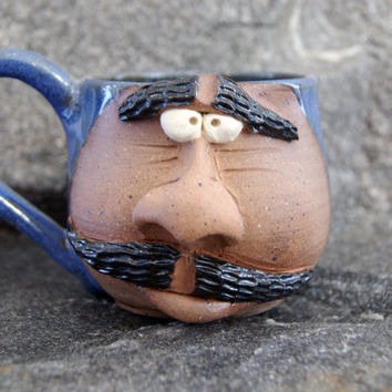 Blue smirking pottery face mug, mustache coffee cup