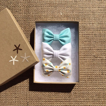 Aqua, white denim, and tiny yellow daisy hair bow set from Seaside Sparrow. These hair bows make a perfect gift for her.