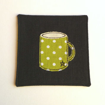 Handmade coaster. Fabric mug coaster. Embroidered fabric coaster with mug design on black linen and green spotty fabric. Made in England.