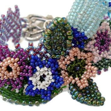 Colorful beaded bracelet decorated with flowers and leaves. Seed beads jewelry