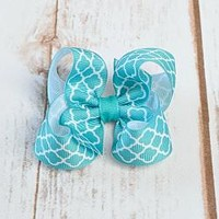 3 inch turquoise hair bow in quaterfoil print is attached to an alligator clip, snap clip or barrette.. Hair Bows for girls and toddlers