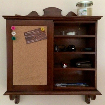 Wall Organizer. Includes cork board, key hooks, shelves. Sliding door gives you two sides to store your items...wallet, keys, pens, glasses.