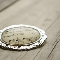 Romantic brooch pin made with vintage sheet music.  Silver plated setting with glass dome.  One of a kind gift