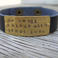 A riveted, brown leather cuff bracelet with hand stamped brass do small things with great love- distressed and embellished wording