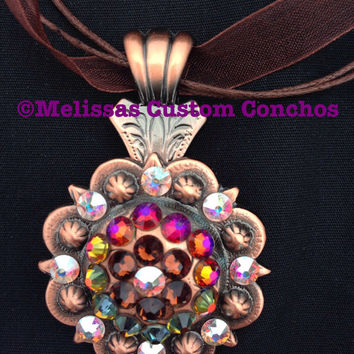 Copper 1-1/2 inch concho necklace. Crystal AB, Smoked Topaz, and Volcano Swarovski crystals. Comes with an 18 inch brown ribbon cord.