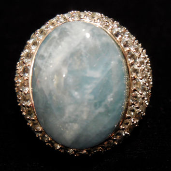 Stunning statement piece, this vintage ring is chic and large. Beautiful Aquamarine cabachon stone with white topaz set in sterling silver.