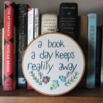 A Book a day keep reality away quote hand embroidery, floral detail in 6 inch hoop, book lover