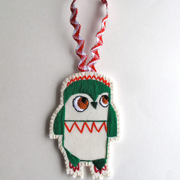 Christmas owl ornament hand embroidered in green with red geometric shapes on cream muslin and cream felt with holiday ribbon loop