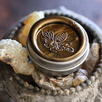 Aumbre Solid Natural Perfume, An Amber Chant - Smokey, incense fragrance in a Round Tin with signature, color coded honey bee wax seal