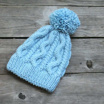 Knit cable hat for women in soft blue color with pompom