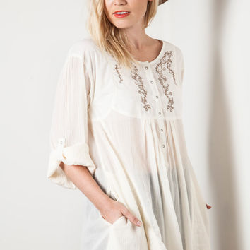 This semi-sheer gauze blouse features textured fabrication, baby doll design, Snaps button-up half way at front top, wide scoop neckline, embroidery design on solid ivory cotton yoke, long sleeves with snap button tab option, oversize construction, two sid