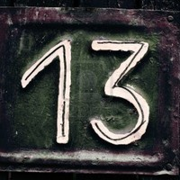 dark desaturated grungy tin house plate number 13 with peeling..