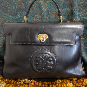 Vintage FENDI black leather handbag in classic Kelly bag style with logo motif at front.