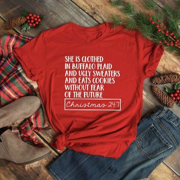 She is clothed in Buffalo Plaid t-shirt Cute Christmas Shirts for Women slogan casual red aesthetic tee bachelorette party tops