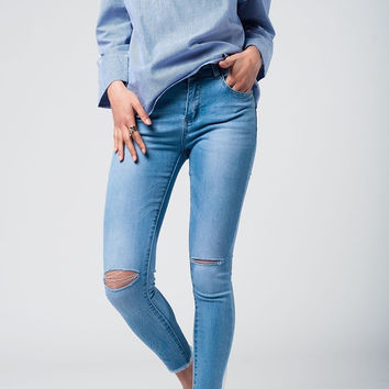 Light wash jeans with broken knees and fringe on the bottom