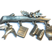 Rare JJ Jonette Jewelry figural pewter bird watcher brooch on branch with owl, field guide, binoculars and song bird dangling charms