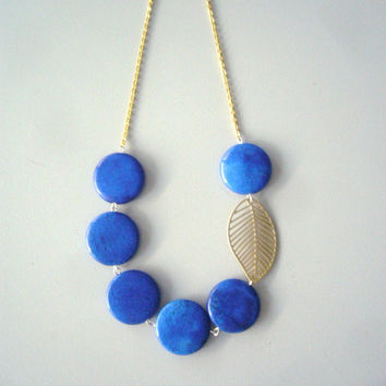 Electric blue necklace with a gold leaf