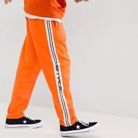 Mennace Jogger In Orange With Taping at asos.com