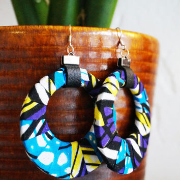 Earrings wrapped in Dutch waxprint. Finished with leather. Circle shaped. Silver colored hooks. Purple, blue and yellow print