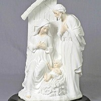 One piece Holy Family in the stable in white with lightly painted features, on a wood base, 12inches.