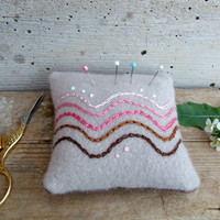 Felted pincushion with abstract embroidery of shading waves in brown and pink. Upcycled wool ecofriendly supplies