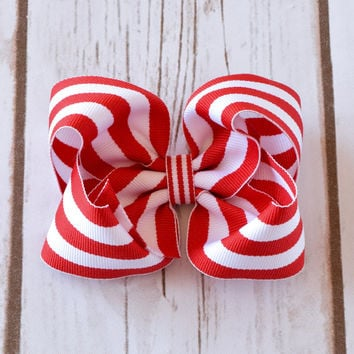 "4 Inch bow in a red and white stripe print is handmade with 1 1/2"" ribbon and is securely attached to a partially lined alligator clip, snap"
