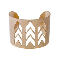 Worn gold tone cuff bracelet with a cutout chevron pattern.
