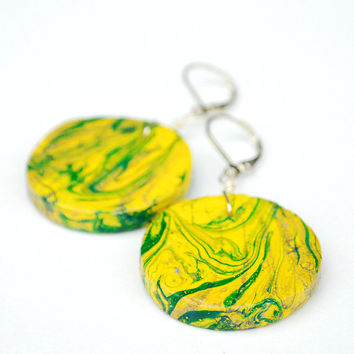 Big circular and bright yellow earrings with green abstract pattern and leverback ear hooks.