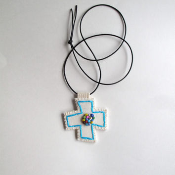 Embroidered pendant necklace in blue with multicolored Ghanaian glass bead embellishment on cream muslin with a black leather cord