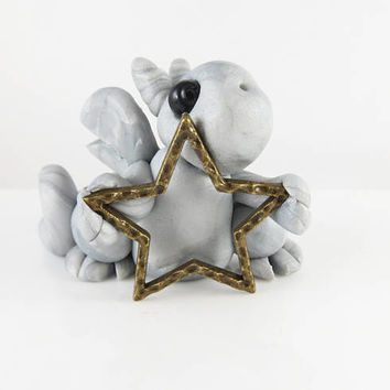 Polymer clay silver baby dragon with a star