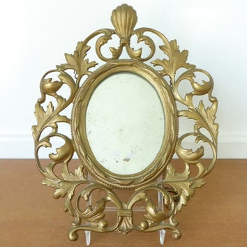 Heavy and ornate gold scrolled mirror with chain for hanging