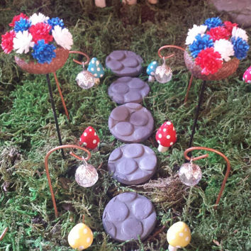 18 piece fairy garden path set. Mushrooms, path lights, stepping stones and 2 acorn planters with red white and blue flowers.