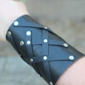 Black leather arm bracer with criss-cross strap detail