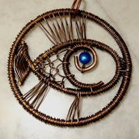 """Copper jewelry pendant """"Blue-Eyed Fish"""", made of solid copper wire and a blue bead."""