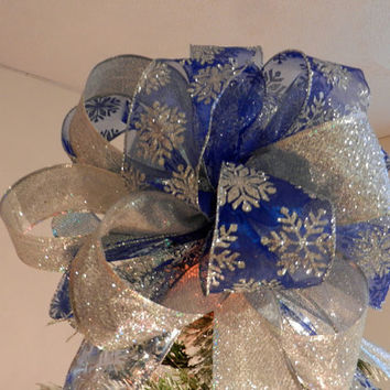 Large Christmas Tree topper bow made of a sheer blue ribbon with silver glitter snowflakes and a silver glitter ribbon