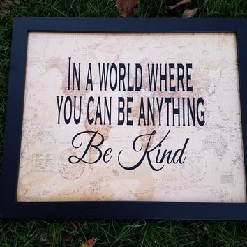 In a World Where You Can Be Anything Be Kind sign with antique world map