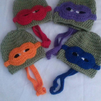 Crocheted Ninja Turtle hats. Green beanie hat with colored mask over eyes.