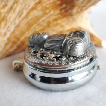 Music box locket,  round locket with music box inside, in silver with Buddha.