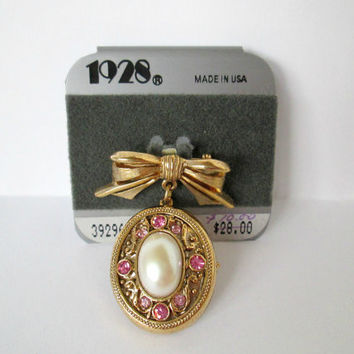 Vintage 1928 Jewelry Locket Brooch Gold Metal Bow or Ribbon Pin with Dangling Locket Embellished with Pink Rhinestones and Pearl New on Card