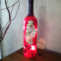 Purple Wine Bottle with white lights. Painted purple and accented with flowers.