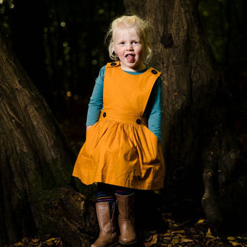 Toddler pinafore dress. Deep gold cotton with black button fastening. Girls dress. Pockets and fully lined.