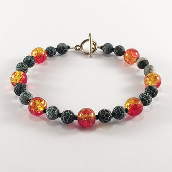Dying Embers bracelet - Fiery red/yellow crackle glass and matte black dragon vein agate bead bracelet with a tarnish-effect toggle clasp