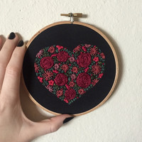 Floral hand embroidery on black fabric in the shape of a heart, 5 inch hoop