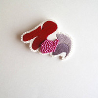 Hand embroidered brooch with unique geometric design using red and mauve cotton threads with pink beads An Astrid Endeavor Spring trends