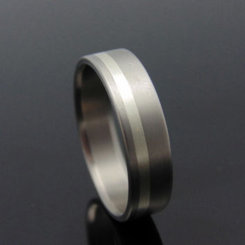 Titanium ring with offset silver inlay