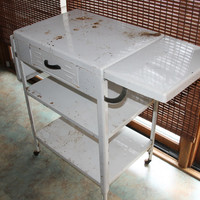 Vintage White Shabby Chic Metal Rolling Cart with Two Shelves, Two Fold Up Leaves and Drawer