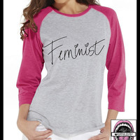 Feminist cursive font. Unisex Baseball 3/4 length sleeve T shirt. PINK or Black sleeve. Womens Clothing. Feminism. Badass.Tough girl. Strong