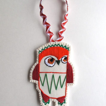 Owl Christmas ornament hand embroidered in shades of reds and greens on cream muslin and cream felt with holiday ribbon loop